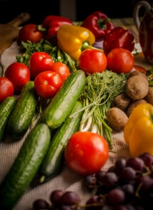 Various vegetables and fruits, bright colors, are on the kitchen table.